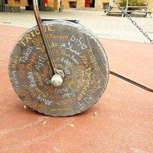 """In 44 Sprachen steht """"Frieden"""" auf dem Mühlstein."""